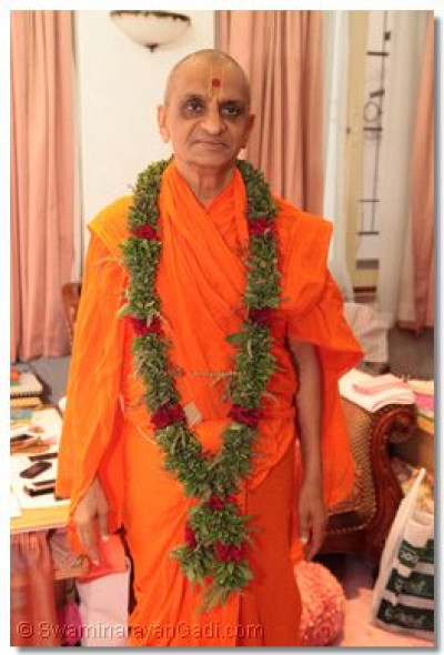 Divine darshan of Acharya Swamishree adorned with a garland made of tulsi.