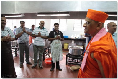 Acharya Swamishree blesses devotees in the kitchen.