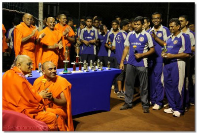 Acharya Swamishree blesses one of the sants for playing in the volleyball tournament.