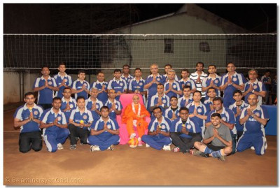 A group photo of Acharya Swamishree with the participants of the volleyball tournament.