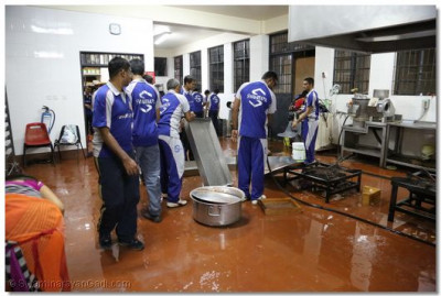 Volleyball players help in cleaning the kitchen after dinner.