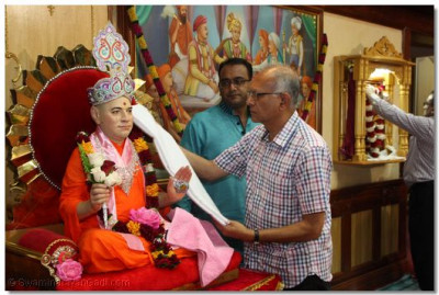 A devotee adorns Muktajivan Swamibapa with a sacred cloth