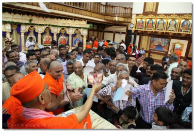 Acharya Swamishree blesses the congregation with His murti.