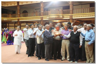 The gents congregation take part in performing aarti