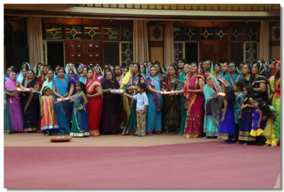 The ladies congregation take part in performing aarti