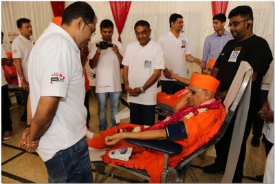A doctor examines Acharya Swamishree's blood pressure