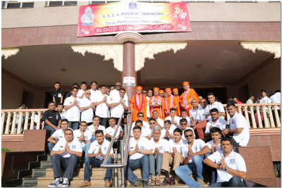 A group photo of volunteers with Acharya Swamishree and sant mandal