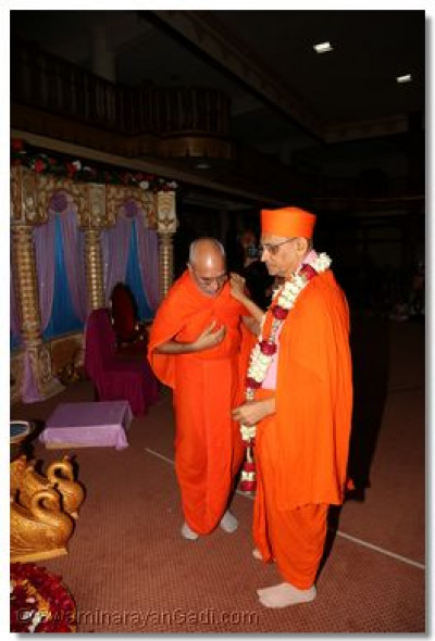 Beloved sant adorns a garland to Acharya Swamishree