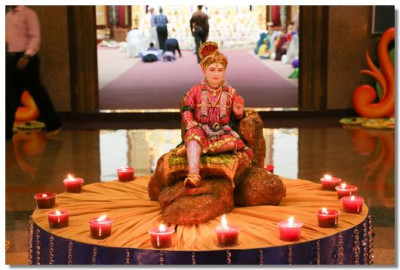 The beautiful murti of Lord Shree Swaminarayan Bhagwan surrounded by candles