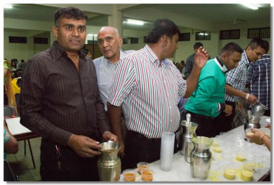 Disciples being served mahaprasad
