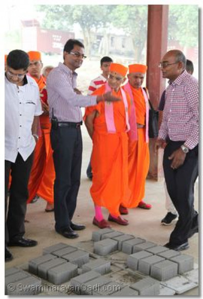 Acharya Swamishree performs padhramni at a work site.