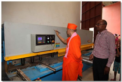Acharya Swamishree performs poojan to new machinery.