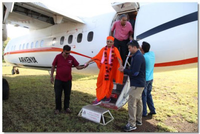 Acharya Swamishree descends from the aircraft