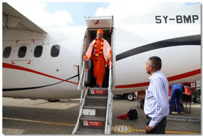 Acharya Swamishree descends the aircraft at the Wilson Airport
