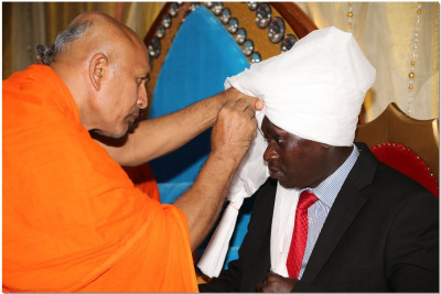 A sant ties a turban for Hon. Joshua Kutuny, chief political advisor-office of The President