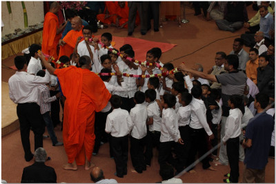 Young devotees carry the garland forward to Acharya Swamishree