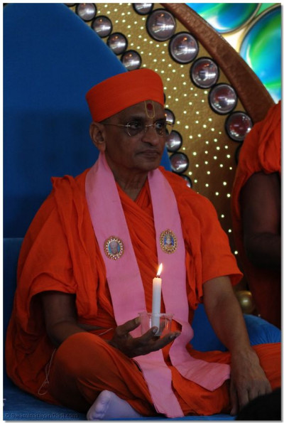 Acharya Swamishree lights a candle in memory of Peshawar attack