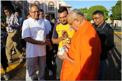 Acharya Swamishree consecrates the football by autographing it