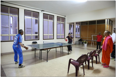 Acharya Swamishree watches the table tennis players play