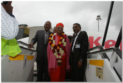 Devotees accompany Acharya Swamishree from the flight
