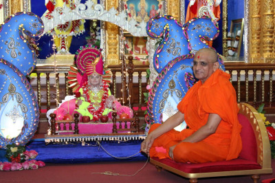 Acharya Swamishree swaying the cradle