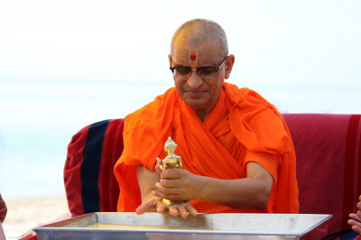 Acharya Swamishree cleanses Shree Harikrishna Maharaj after panchamrut snan