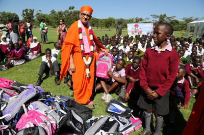 Acharya Swamishree presents school bags, books and stationery to over 400 students from three schools within the area