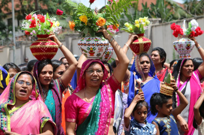 Devotees carry urns to welcome Acharya Swamishree and sant mandal