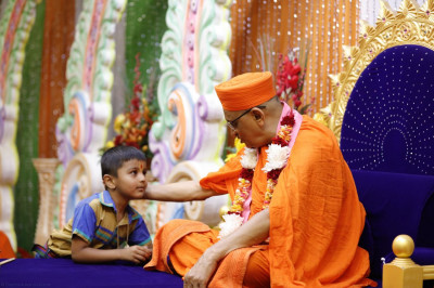 Acharya Swamishree blesses a young devotee