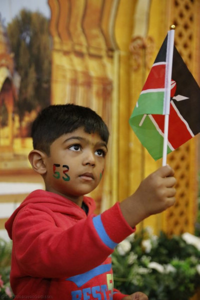 One of the young devotees holds the Kenyan flag with passion