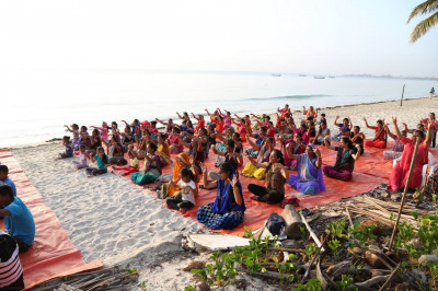 Devotees enjoy the yoga at the beach