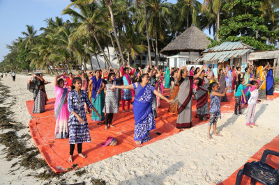 Devotees perform morning yoga at the beach