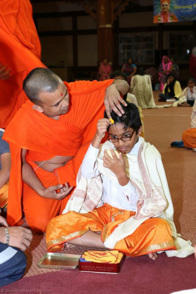 A young devotee being assisted by a sant to commence the pooja