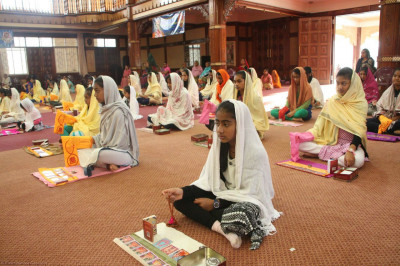 Young devotees perform pooja at the Sadhbhav Amrut Parva Satsang Shibir