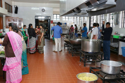 Devotees assist in the kitchen for breakfast