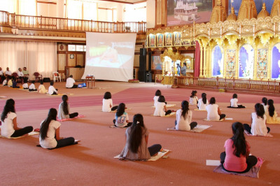 The young devotees viewing a video clip of Acharya Swamishree performing pooja vidhi