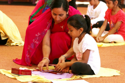 Volunteers help the young devotees prepare for their pooja vidhi