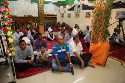 Devotees keenly listen to the divine discourses of Acharya Swamishree