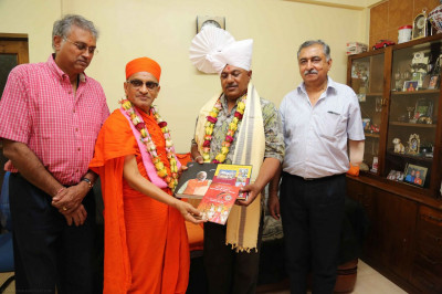 Acharya Swamishree presents the guest with consecrated gifts