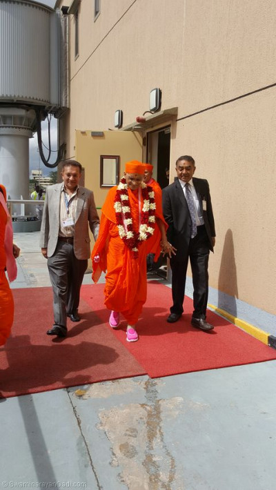Devotees escort His Divine Holiness Acharya Swamishree towards the VIP lounge