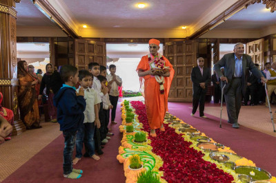 His Divine Holiness Acharya Swamishree blesses the devotees as He walks on the decorated walkway