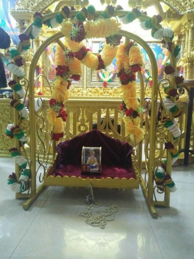 Lord Shree Swaminarayanbapa Swamibapa giving Divine darshan on a hindolo made of artificial flower garlands
