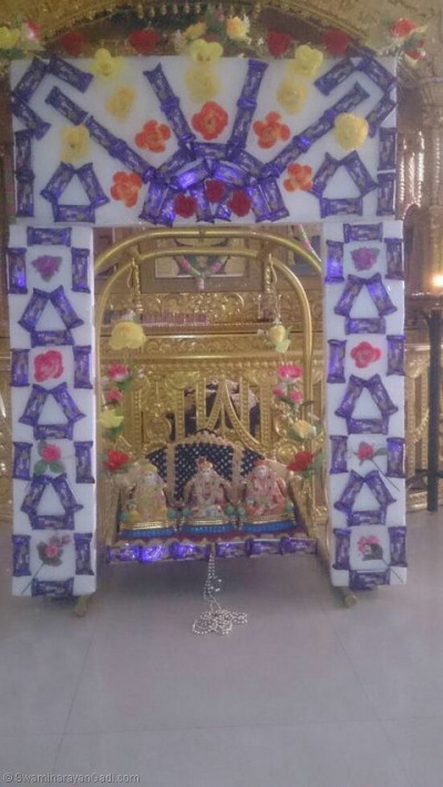 Lord Shree Swaminarayanbapa Swamibapa giving Divine darshan on a hindolo made of sweets and chocolates