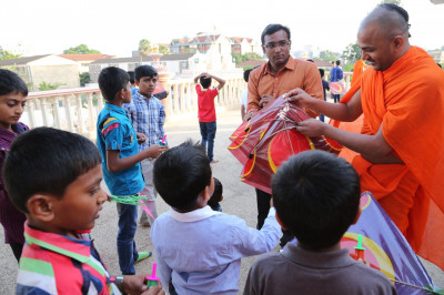 A sant distributing kites to the young devotees