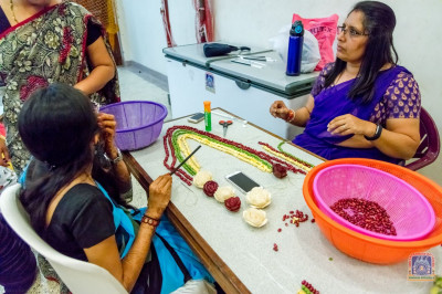 Devotees preparing a garland made of vegetables for H.D.H Acharya Swamishree Maharaj