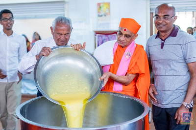H.D.H Acharya Swamishree Maharaj and the hosts of the event pour ghee for tempering