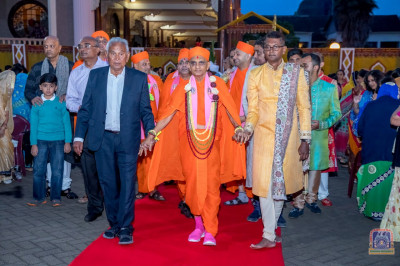 Devotees escort H.D.H Acharya Swamishree to the traditionally decorated stage