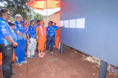H.D.H Acharya Swamishree having a look at the schematic diagram of the ground pavilion