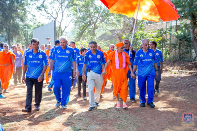 Devotees escort H.D.H Acharya Swamishree towards the ground