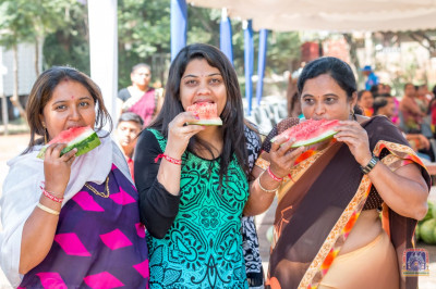Devotees enjoy the watermelon being served